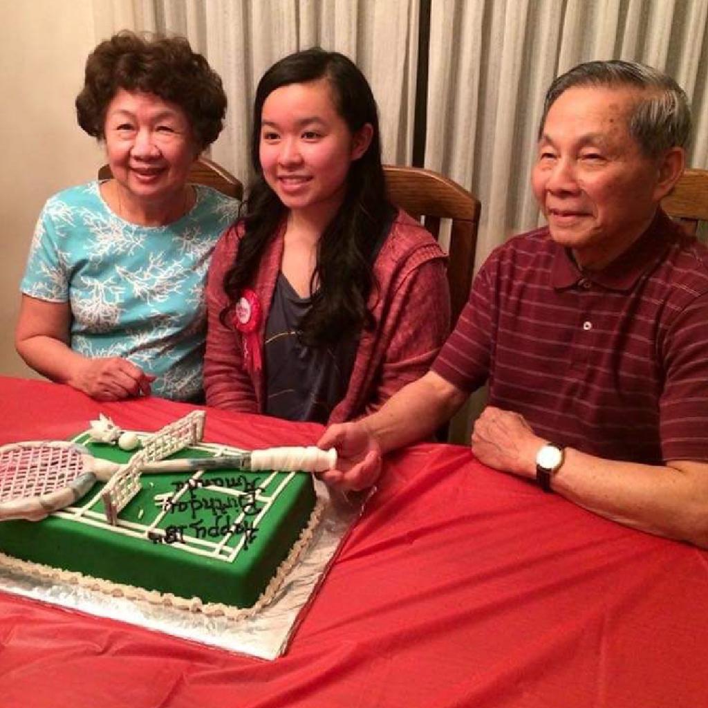 Amanda sitting between her grandma and grandpa celebrating her birthday.