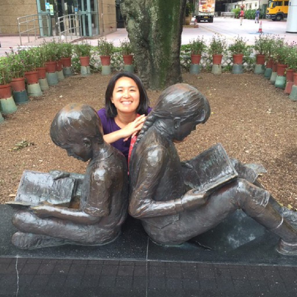 Amy posing behind an art sculpture of two children reading books.